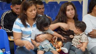 Mothers and children wait to be assisted by volunteers in a humanitarian centre in the border town of McAllen, Texas on 14 June 2018.