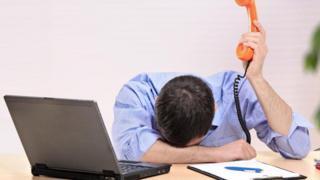Un empleado con expresión de desesperación, frente a una laptop y con un teléfono
