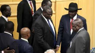 South Sudan rebel leader Riek Machar (centre) shakes hand with South Sudan President Salva Kiir (in black hat) at a peace summit attended 17/08/2015