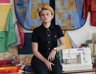 Poppy Nash sitting next to her sewing machine amongst her materials