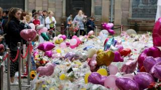 """Balloons and flowers at a makeshift memorial at St Ann""""s Square"""