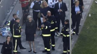 Theresa May meets firefighters at the scene