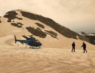 A helicopter and two people are seen on snow