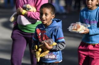 Migrant children carry bananas and other food items in the sports stadium in Mexico City where they are sheltering