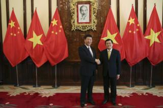 Chinese President Xi Jinping, left, and Vietnamese President Truong Tan Sang shake hands at the Presidential Palace in Hanoi, Vietnam, Friday, 6 November 2015
