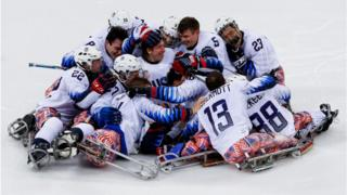 The United States Ice Hockey team embrace each other on the ice after they win gold against Canada