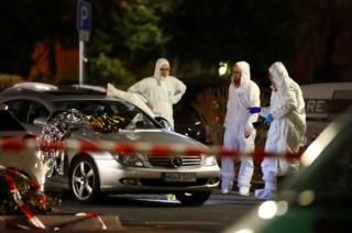 Forensic experts examine a damaged car after a shooting in Hanau near Frankfurt, Germany, 20 February 2020.