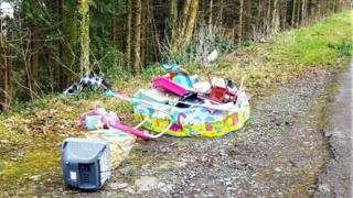 A paddling pool and TV dumped in a lay-by