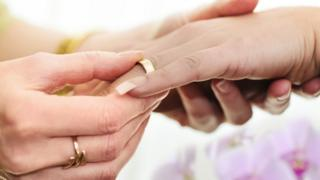 Women exchanging wedding rings