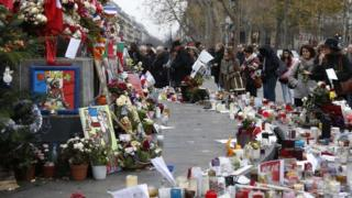 People gather in front of a makeshift memorial at the Place de la Republique in Paris on 13 December 2015, a month after the Paris terror attacks that claimed 130 lives