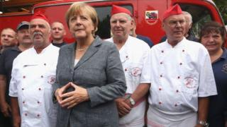 Angela Merkel posing with a group of men in white and red uniforms with red caps, 3 August