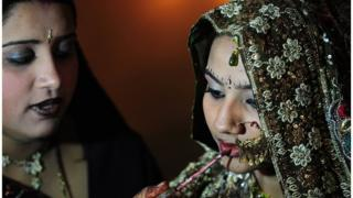 A Pakistani Hindu bride gets final touches from a relative at a mass-wedding ceremony in Karachi on January 2, 2015.