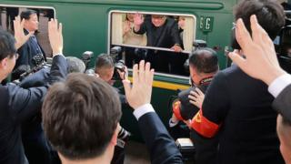 This picture from North Korea's official Korean Central News Agency (KCNA) shows North Korean leader Kim Jong Un waving from his train as it prepares to depart from Beijing railway station.