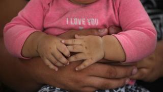 Una madre tiene en brazos a su bebé