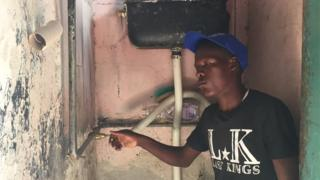 A man turning on the tap in Zimbabwe.
