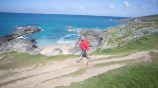 A man takes a stroll at Fistral beach in Newquay, Cornwall