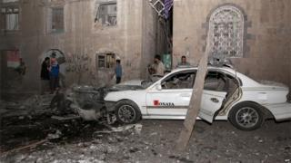 The wreckage of a car is seen at the site of a car bomb attack in the capital Sanaa on 29 June 2015.