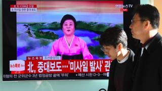 路人经过一个电视屏幕,屏幕上正在播放朝鲜洲际弹道导弹的新闻。