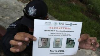 "A police officer shows a reward notice as investigators and members of Federal Police continue investigations into the escape of drug trafficker Joaquin ""El Chapo"" Guzman, in Amolaya, Mexico, 16 July 2015."