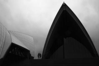 Two people share an umbrella to shelter outside the Sydney Opera House