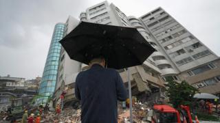 在雨中,一名男子在灾场祈祷。