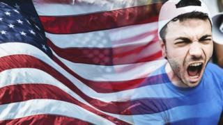 Man shouting in front of an American flag