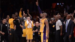 umukinnyi wa Los Angeles Lakers Kobe Bryant (24) apepera abafana muri sitade ya Staples Center nyuma y'umukino bakinaga na Utah Jazz