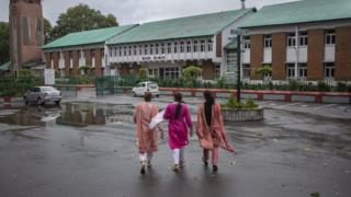 Women walk towards a school in Srinagar