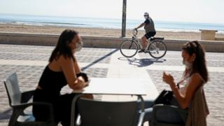 Women wearing protective masks sit on a terrace of a restaurant at Malvarrosa beach, as some Spanish provinces are allowed to ease lockdown restrictions during phase one, amid the coronavirus disease (COVID-19) outbreak, in Valencia, Spain May 18,
