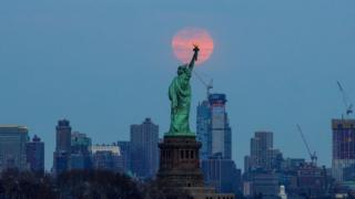 The last supermoon of 2019 'Super Worm Equinox Moon' rises behind the Statue of Liberty in New York