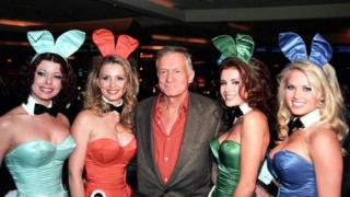 Hugh Hefner with four women in Playboy uniforms