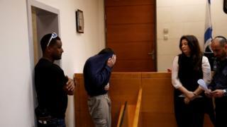 Michael Ron David Kadar (menutup muka) dituduh membuat ratusan ancaman hoax bom.