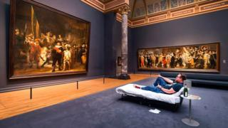 """Stefan Kasper lying in a bed in front of the painting """"The Night Watch"""" by Dutch painter Rembrandt at the Rijksmuseum of Amsterdam on June 1,"""