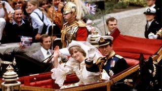 The Prince and Princess of Wales wave in an open-top carriage on their wedding day