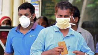 Indian residents wear face mask outside the Medical College hospital in Kozhikode on May 21, 2018