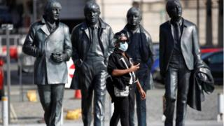 Beatles statue and woman wearing mask