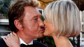 "Cast member Johnny Hallyday and his wife Laeticia kiss during red carpet arrivals for the screening of the film ""Vengeance"""