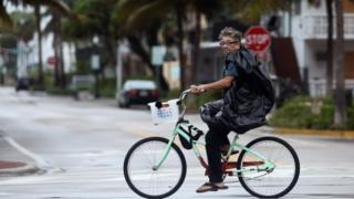 Homem anda de bicicleta por Miami Beach