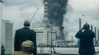 Scene from Chernobyl showing actors looking at smoke coming from power station