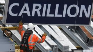 A construction worker guides down a sign showing the name of Carillion