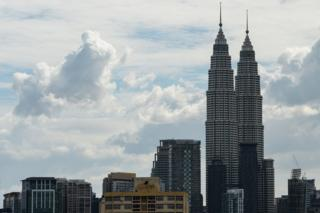Malaysia's landmark Petronas Twin Towers (R) and commercial buildings are seen on a clear day in Kuala Lumpur on 29 October 2015.