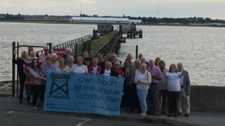 Campaigners celebrate by the pier