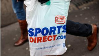 A plastic Sports Direct bag is carried by a shopper.