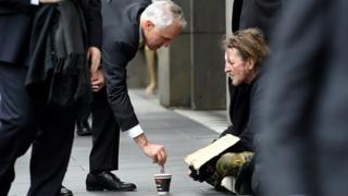 Prime Minister Malcolm Turnbull gives $5 to a beggar