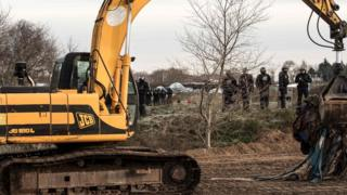 "Bulldozer clears part of the makeshift Calais camp called the ""Jungle"""
