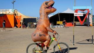 डायनासोर के कॉस्ट्यूम में साइकिल चलाता व्यक्ति