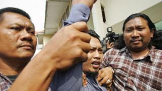 Hassan raising his fist in defiance as he leaves court