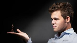 Magnus Carlsen segura uma peça de xadrez com a palma da mão e em posição de perfil