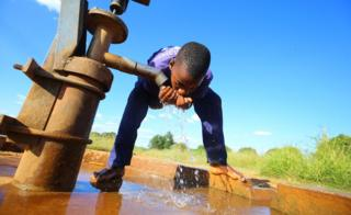 A boy drinks water from a public borehole in Chegutu, 100 km west of the capital, Harare, Zimbabwe, 22 January 2018.