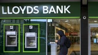 A man walks past a Lloyds Bank branch
